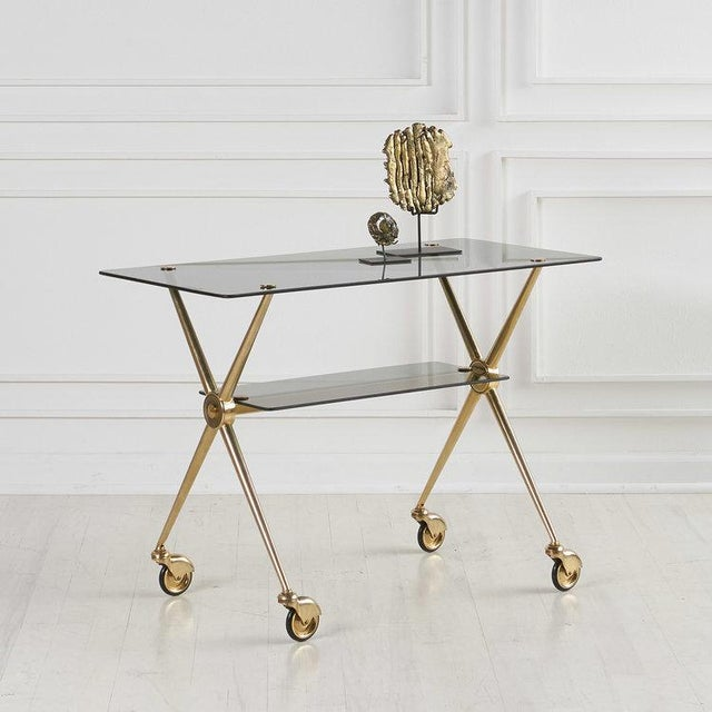 An elegant two tiered X shaped Brass Side table with smoked glass shelves, fastened with brass hardware. In the style of...