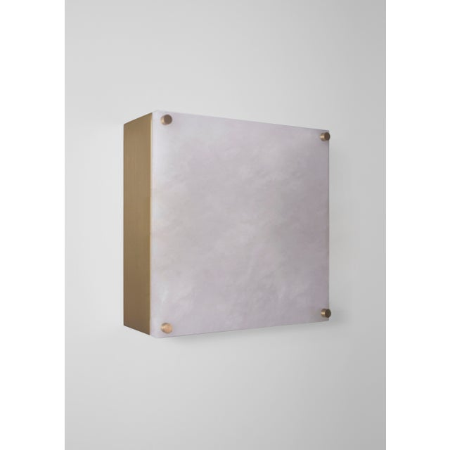 This contemporary light made of brushed brass and alabaster is part of the Orphan Work brand and can be used as a wall...