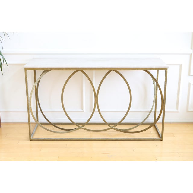 Overlapping gold circles on the open metal frame create a distinctive style using symmetry and geometry. The white marble...