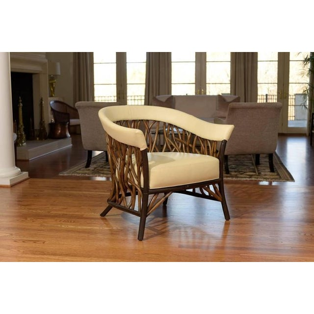 A fabulous organic pair of lounge or club chairs by Palecek. Handsome barrel back design with a beautiful vine-like rattan...