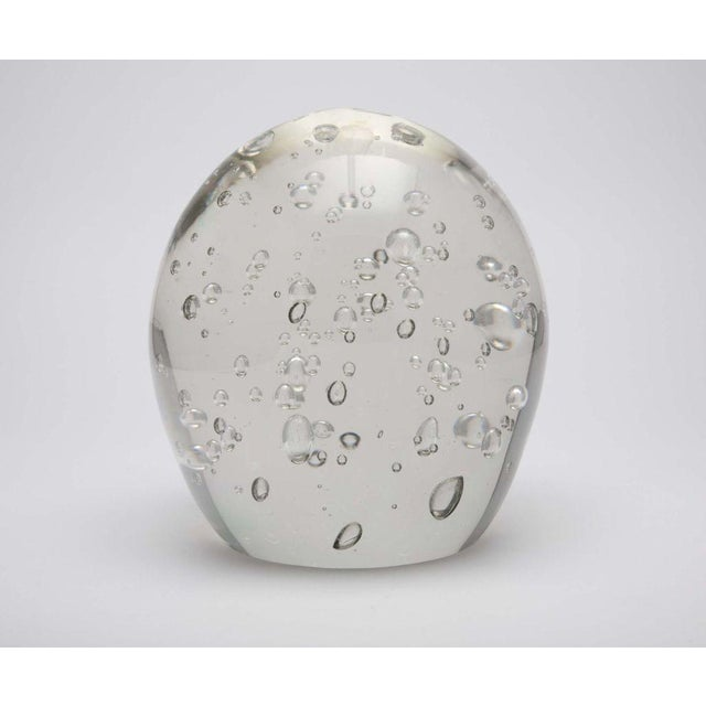 A glass object or large paperweight in solid clear glass with controlled air bubbles that float within its egg shape. Has...