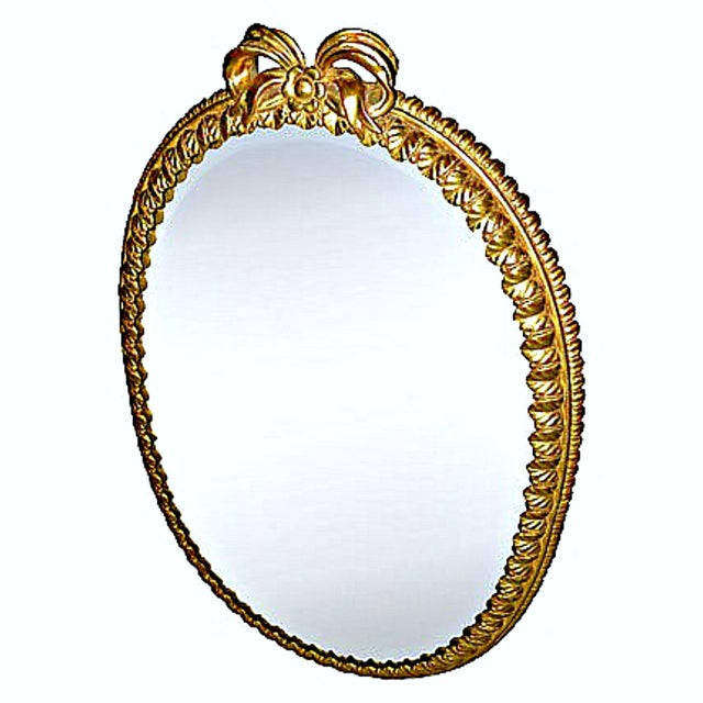 This medallion-shaped, beveled mirror features a carved wood, gilt frame. The carved frame is composed of an elaborated...