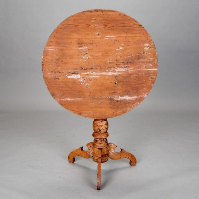 Early 19th century Swedish table has a round tilt top, turned leg, tri-footed base and original red painted finish. Circa...
