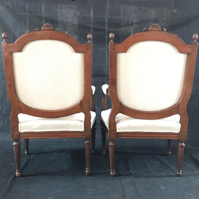 A stunning sturdy pair of elegant French Louis XVI fauteuils armchairs having intricately carved details of flowers,...