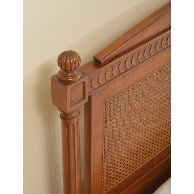 A vintage Federal style king size headboard by Henredon. This headboard features a broken pediment over a cane panel...
