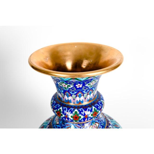 Large vintage gilt brass interior cloisonné exterior decorative vase / piece with floral design details. The vase is just...