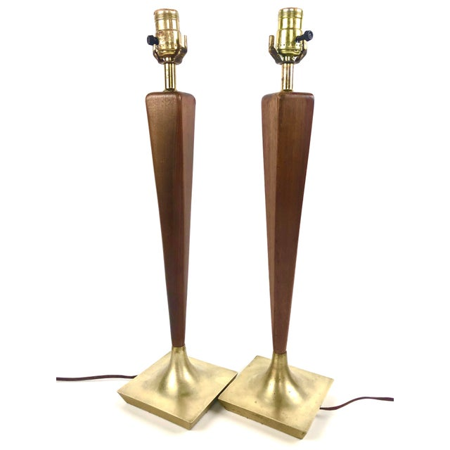 Gorgeous pair of Mid Century (c. 1960) walnut and brass table lamps by Laurel, USA. These lamps feature a walnut stem...