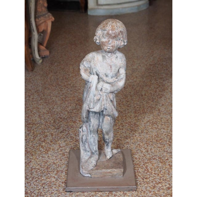 A lead statue of a sweet girl child holding a fish in her draped garment. The statue stands on a square iron base....