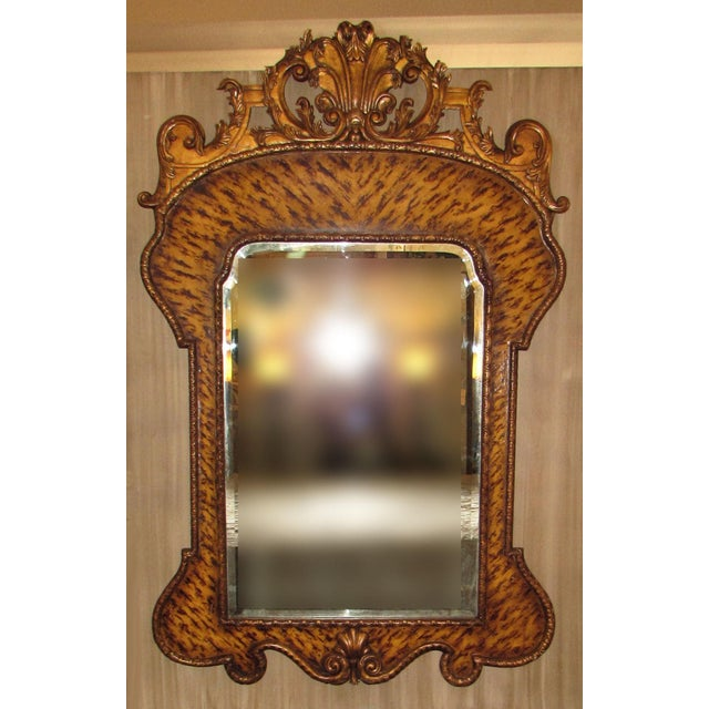 A gorgeous hand-carved mirror by Theodore Alexander with an exotic finish. Condition is excellent with a few small spots...