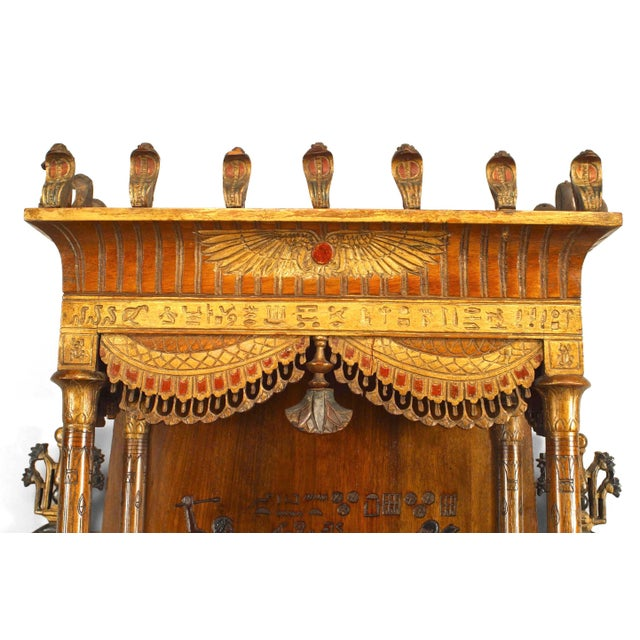 Egyptian style painted hanging wall cabinet with carved and decorated figures and two front doors above a single drawer...