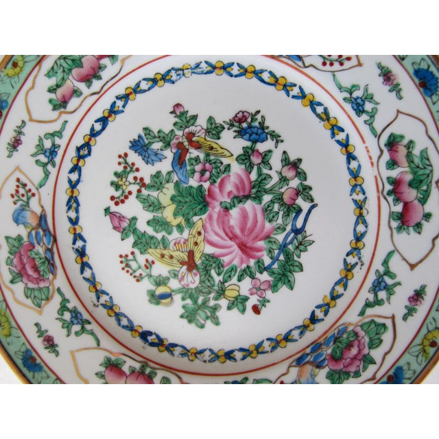 Beautiful decorative Chinoiserie wall plate with a mint green border and pink, blue and green flowers and butterflies.