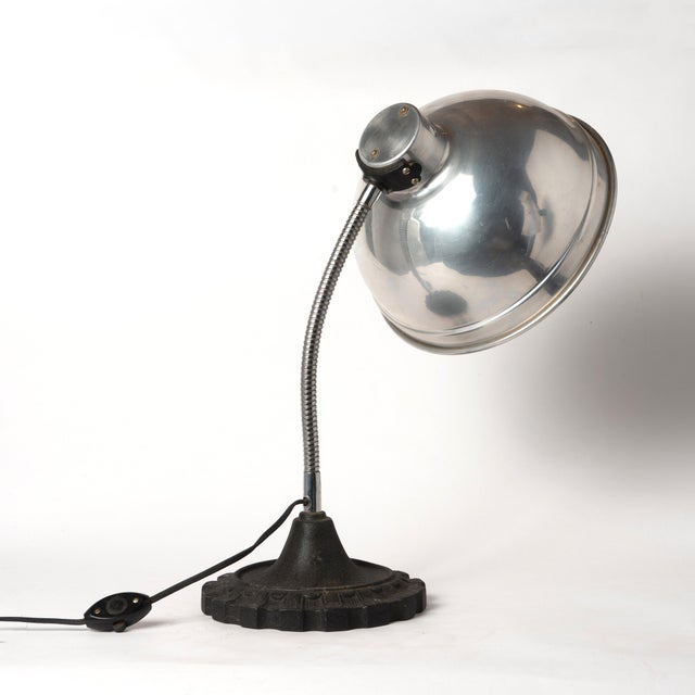 A vintage industrial table lamp with an aluminum shade, gooseneck and cast iron base.