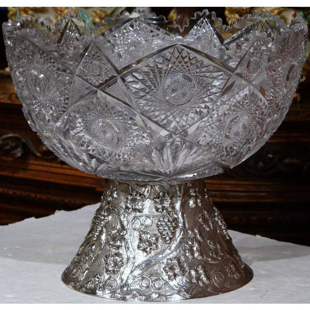 Elegant antique cut-glass punch bowl with separate silver repousse base from France, circa 1890. The base features...