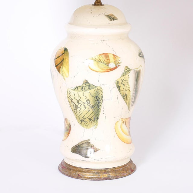 Midcentury pair of Italian table lamps with a Classic form and decorated with sea shells in a reverse decoupage technique...