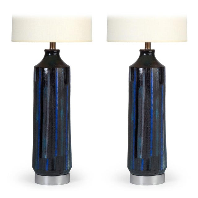 A cylindrical, textured pair of table lamps with incised vertical lines and blue, grey and dark navy painted panels, the...