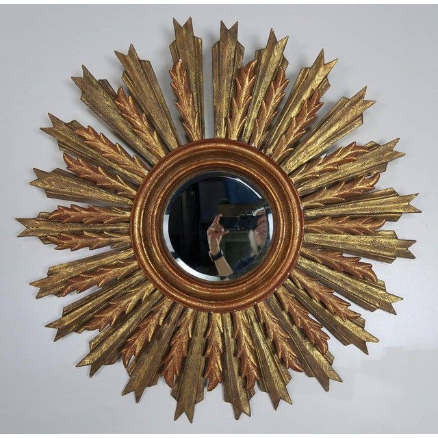 Spanish carved gilt wood sunburst mirror with beveled glass.