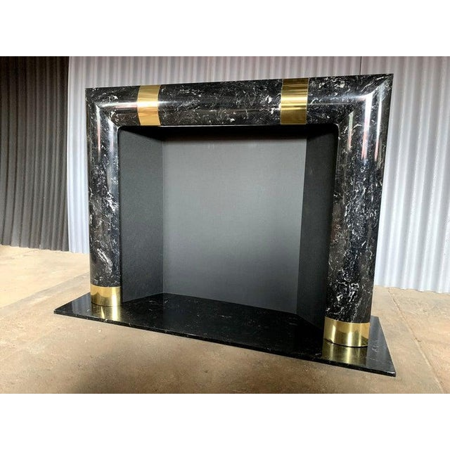 Beautiful and incredible fireplace surround with brass trimmings. This fireplace surround sits on a marble platform....