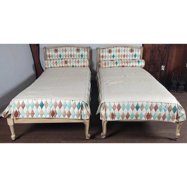 Pair of French Louis XV style twin beds with harlequin fabric upholstered headboards, neck rolls, and bedspreads. Fabric...