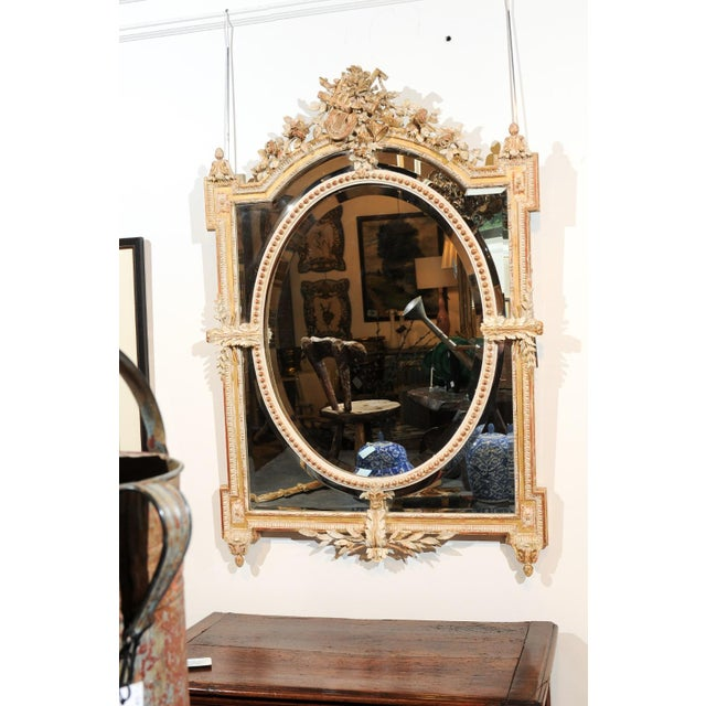"A French Louis XVI style parcel-gilt and painted wood mirror ""à pareclose"" from the 19th century, with hand-carved crest,..."