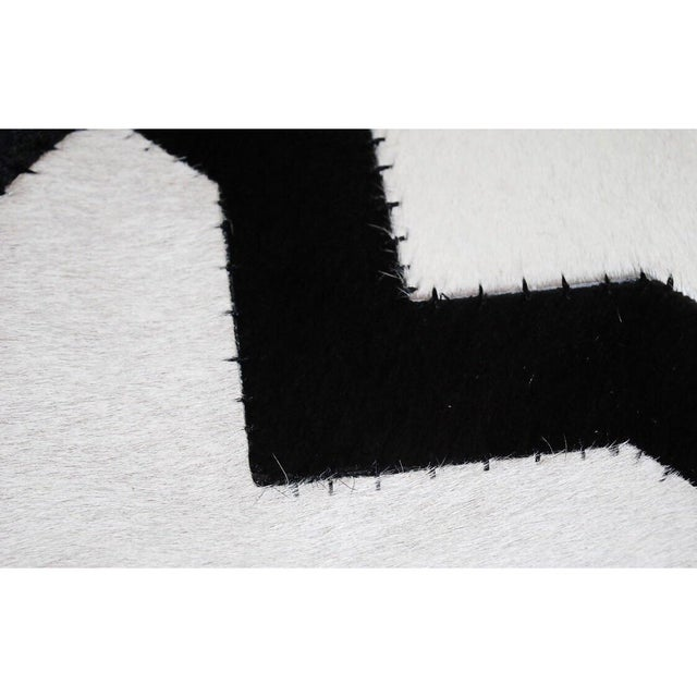 Each ottoman features a cowhide cushion with a Moroccan style design with black and white hues and black sides. Any...