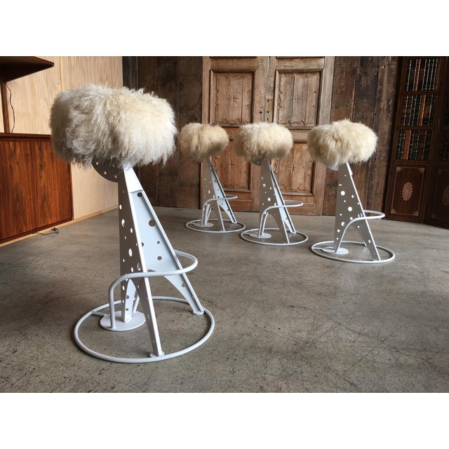 Set of four stools with cream color Mongolian lambs wool seats and satin white steel base.