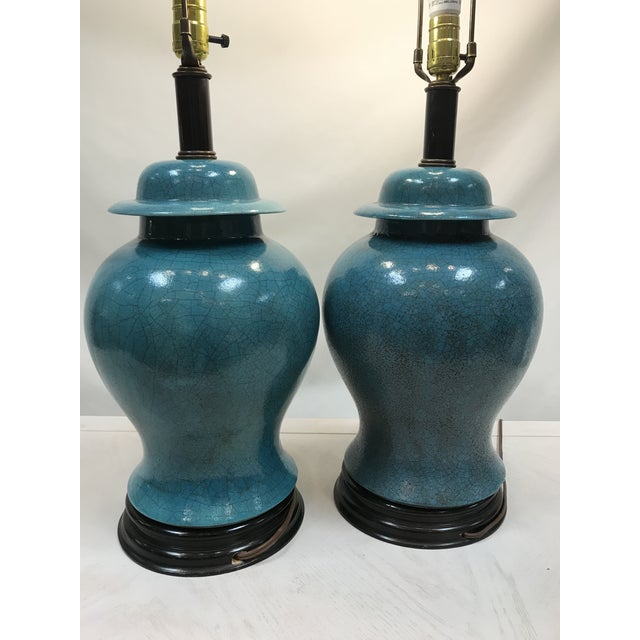 In Great condition crackle finish smooth to the touch. The bases and finial are dark wood with crisp white shades.