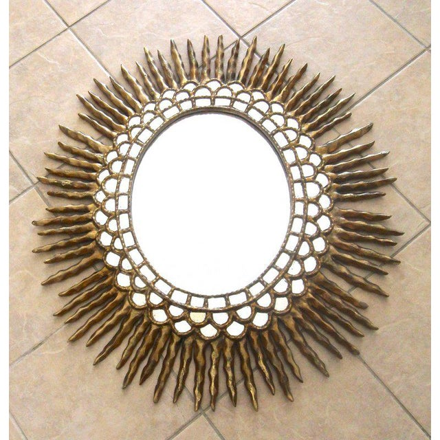 Huge hand carved oval shaped colonial Spanish style wall mirror in gold gilt finish. Smaller rows of small inset mirrors...