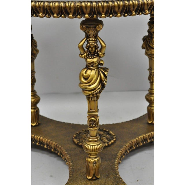 Vintage gold figural side table from the '60s. Item features metal female figural legs, decorated skirt, and shaped glass...
