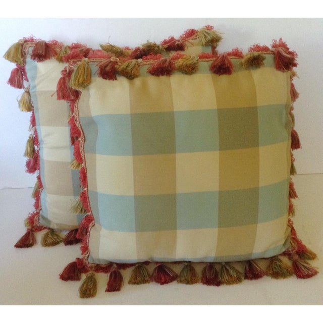 This pair of pillows has the neutral hues of blue, gold and green woven into an overlapping plaid and all trimmed with a...