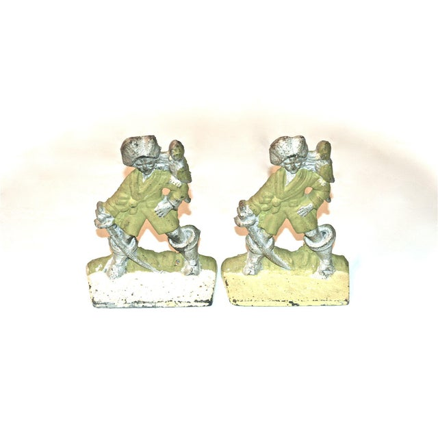A parrot perches on a pirate's shoulder on this pair of cast iron bookends, circa 1920s. Made in America. Vibrantly...
