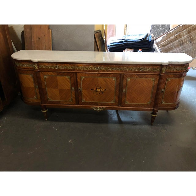 20th C. French Louis XVI marble top buffet with marquetry inlay and carved sides, solid mahogany with satin wood and fruit...