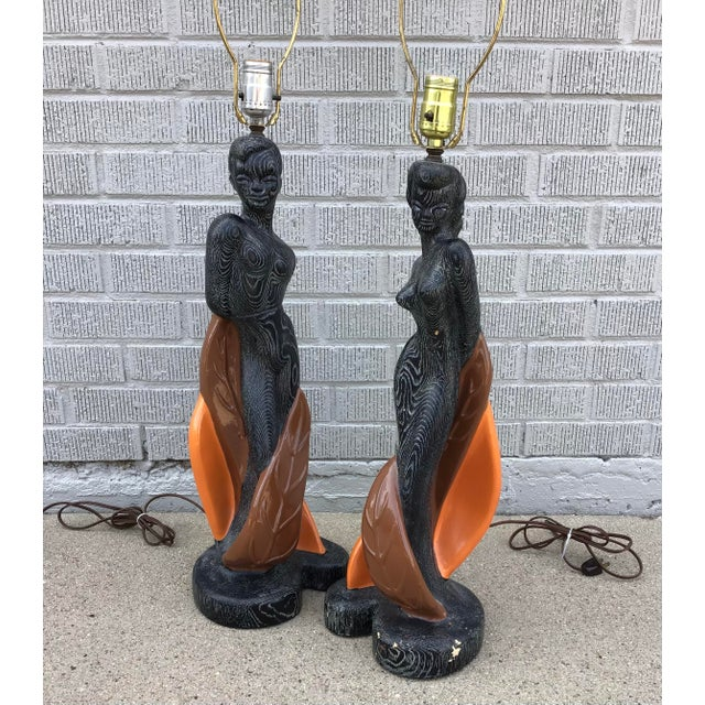 """A gorgeous pair of intricately carved chalkware lamps, stamped """"Reglor of California 1951"""". Black textured base with..."""