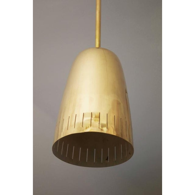 This brass polished bell-shaped pendant in the style of Paavo Tynell was made by JT Kalmar in the early 1950s, and is...