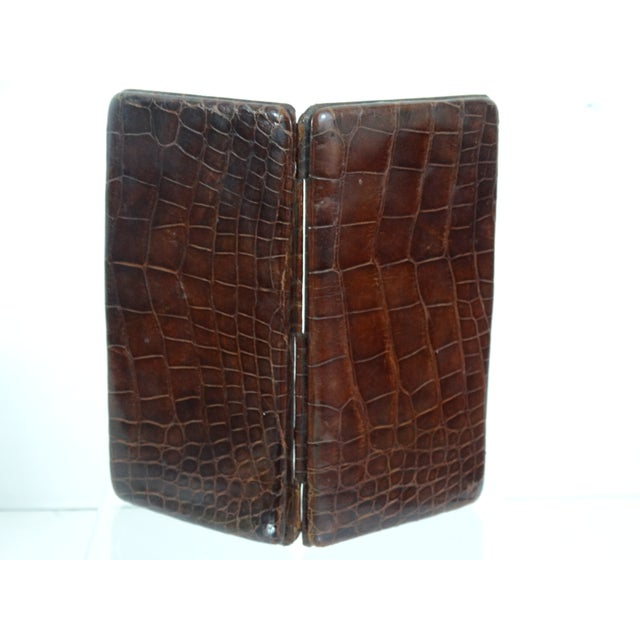 A handsome French genuine crocodile skin card case in lustrous cognac colored crocodile. This early 20th-Century, fine...