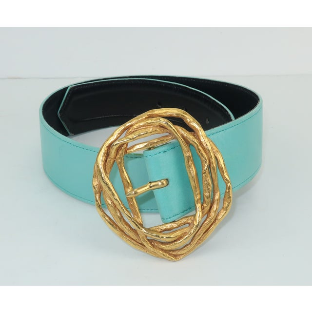 Christian Lacroix pairs a pale aqua blue leather belt with a sculptural gold tone buckle that resembles twisted vines for...