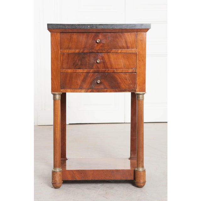 A stately three drawer mahogany bedside table, with black fossil marble top, from 1910s France. The table was made in the...