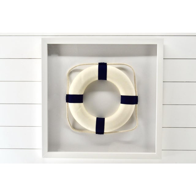Very cool nautical coastal look. White life ring with blue strapping. Professionally framed in a all wood white shadow box...