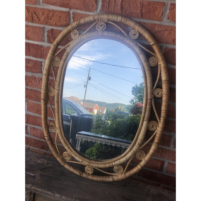 Lovely woven wicker curly cue peacock mirror from the 70's. It has some wear, but overall excellent condition for age....