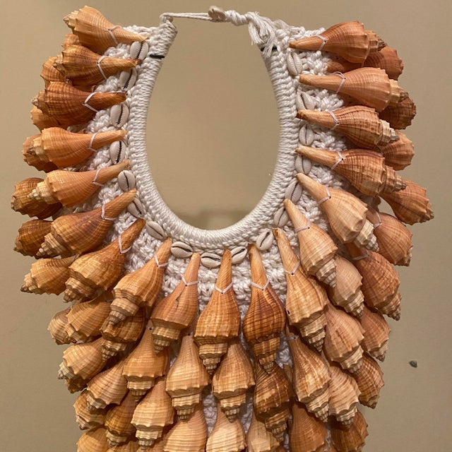 """Natural seashell necklace on metal stand. Hand tied on hand knitted back panel. Necklace dimensions 16.5"""" wide 26"""" tall..."""