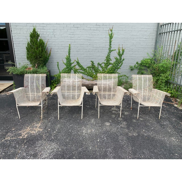 Set of four antique French chairs fabricated of perforated steel and iron. Gorgeous layers of paint are layered on these...