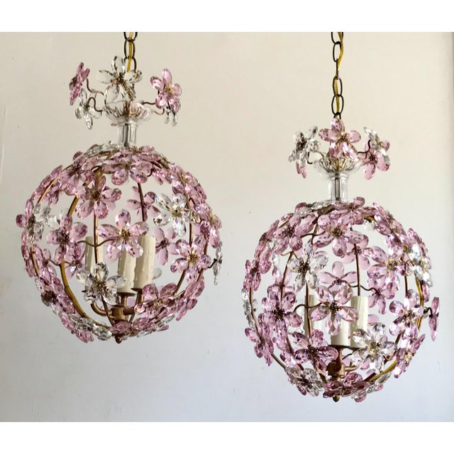 Gorgeous contemporary gilt iron globe chandelier covered with pink and clear flowers made from faceted crystal prisms....