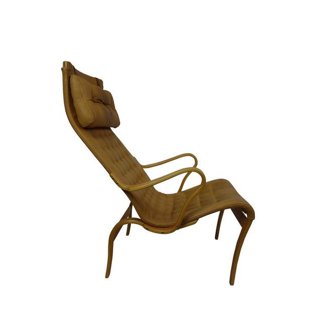 This is a sleek midcentury Miranda lounge chair by Bruno Mathsson in lamented bent birchwood in its original tan leather...