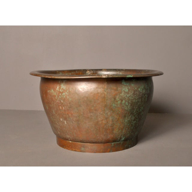 Handsome hammer worked copper pot for patio or indoor enjoyment. Dovetail joinery binds the pot at two sides.