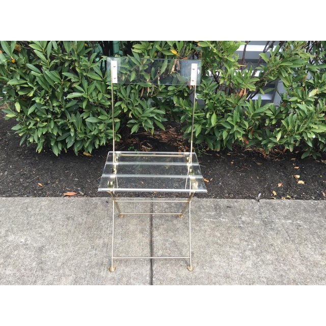 Fabulous vintage acrylic folding chair from France, very chic, has a brass frame and base with acrylic seat and back,...