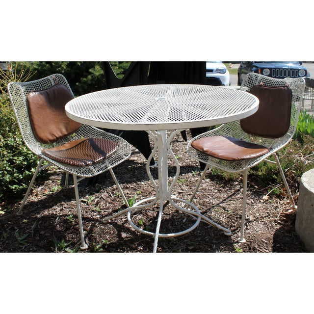 For your consideration is a wonderful wrought iron patio set, including a table and two chairs with rare pads made of...