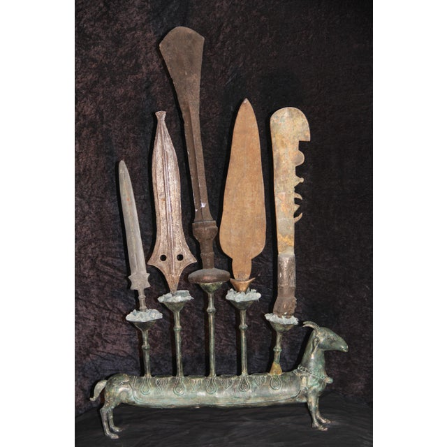 Five antique daggers & machetes from the four corners of the Earth are bonded upright on a metal vintage replica goat...