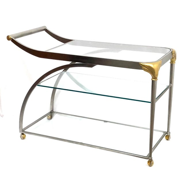 Large scale, streamlined and impressive piece in satin stainless and gold tone. Three clear glass shelves. Vintage...