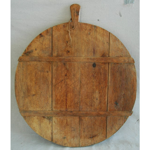 Large 1920s French hand-made joined pine wood slat cutting cheese bread board with handle and leather cord. No maker's...