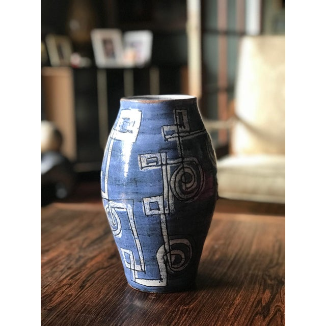 I am offering this wonderful vibrant blue vase with a fun abstract and somewhat geometric design. This piece is...