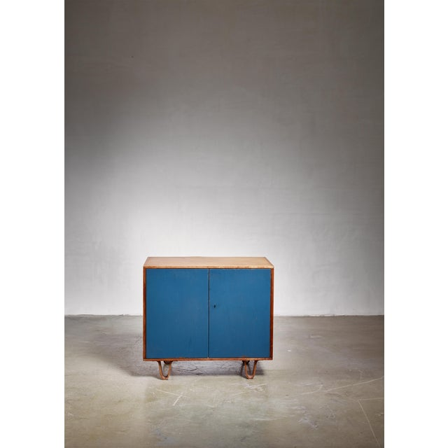 An early model CB-02 cabinet by Dutch designer Cees Braakman for Pastoe on bent plywood legs. The cabinet has petrol blue...
